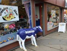 Image shows the Wooden Shoe store front. In front of the store is a statue of a blue Beemster cow.